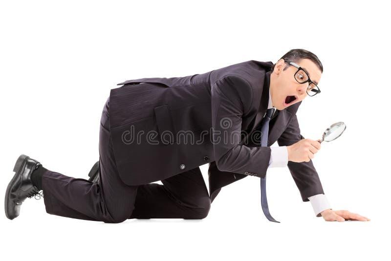 Homem que procura por algo com uma lente de aumento imagens de stock royalty free