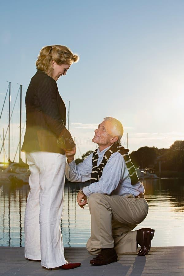 Homem que propõe à mulher no porto imagens de stock royalty free