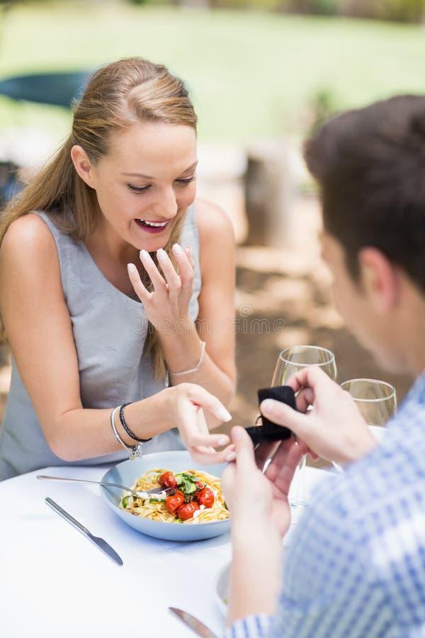 Homem que propõe ao anel de noivado de oferecimento da mulher fotos de stock royalty free