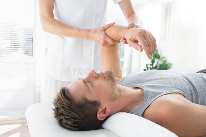Homem que recebe a massagem da mão do terapeuta fotos de stock royalty free