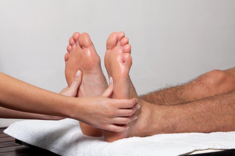 Homem que recebe uma massagem do pé imagens de stock