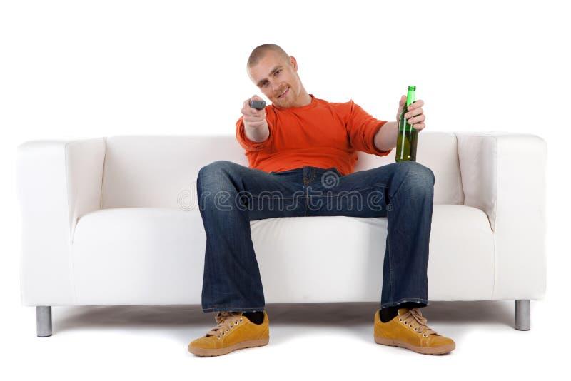 Homem que relaxa com cerveja no sofá imagem de stock royalty free