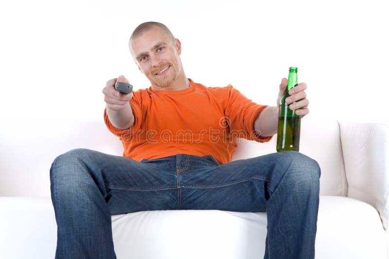 Homem que relaxa com cerveja no sofá fotografia de stock royalty free
