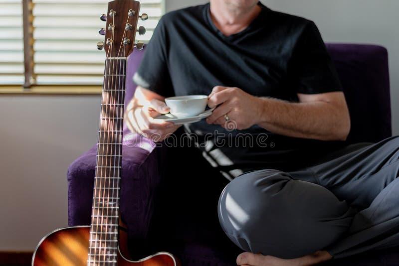 Homem que relaxa com xícara de café e guitarra fotografia de stock royalty free