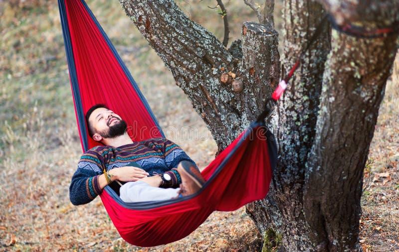 Homem que relaxa em um hammock fotografia de stock