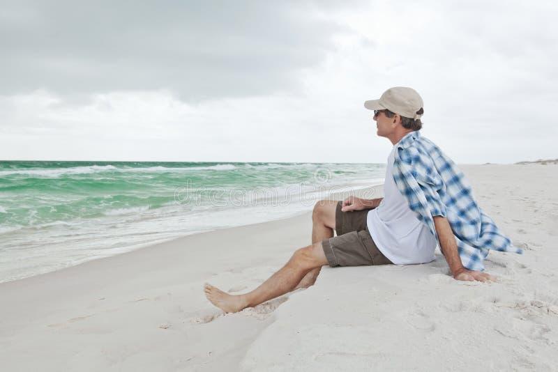 Homem que relaxa em uma praia bonita fotos de stock