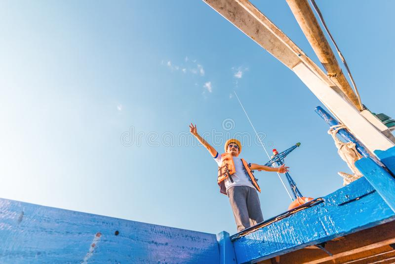 Homem que relaxa felizmente no iate do veleiro das f?rias que tem um resto no fundo do barco do ver?o e do c?u azul imagem de stock royalty free
