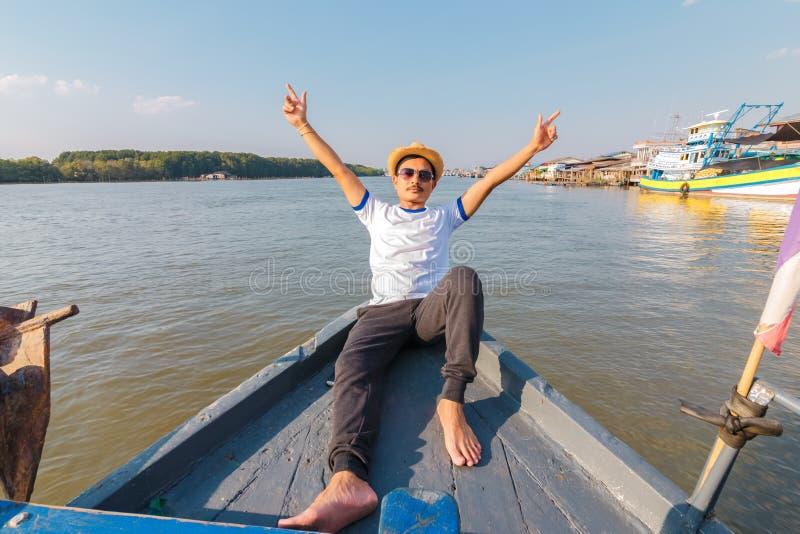 Homem que relaxa felizmente no iate do veleiro das f?rias que tem um resto no fundo do barco do ver?o e do c?u azul fotos de stock royalty free