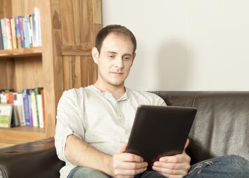 Homem que relaxa lendo um eBook imagem de stock royalty free