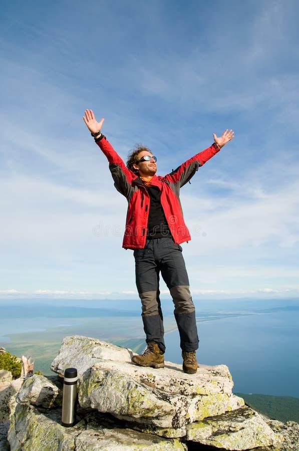 Homem que relaxa na parte superior da montanha foto de stock royalty free