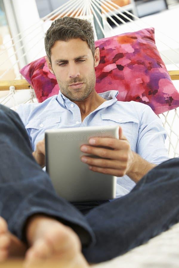 Homem que relaxa na rede do jardim usando a tabuleta de Digitas foto de stock