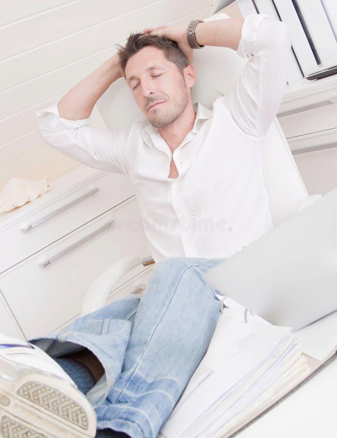 Homem que relaxa no escritório foto de stock royalty free