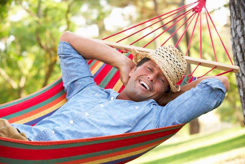 Homem que relaxa no Hammock foto de stock royalty free