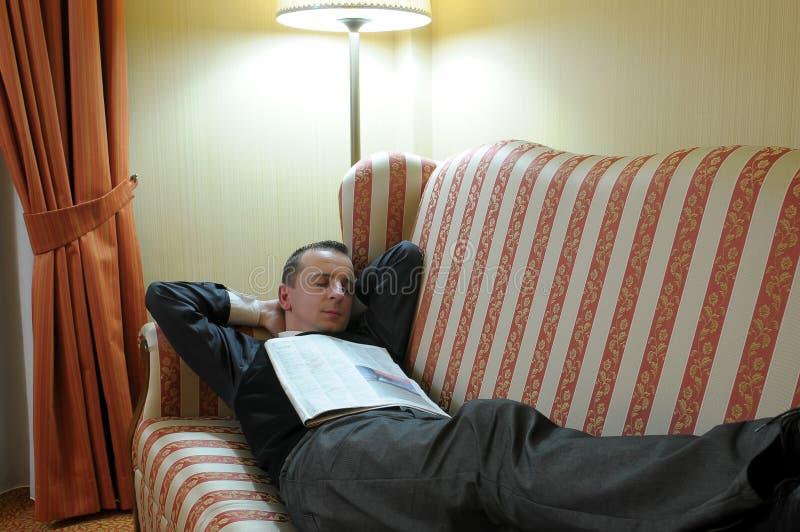 Homem que relaxa no sofá fotografia de stock royalty free