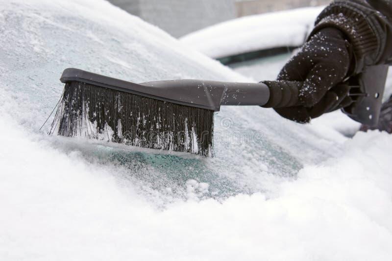 Homem que remove a neve e o gelo do indicador imagem de stock royalty free