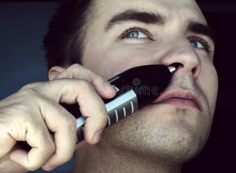 Homem que remove o cabelo de nariz foto de stock