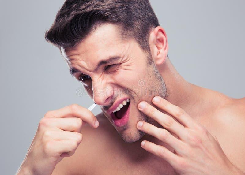 Homem que remove o cabelo de nariz com a pinça fotos de stock