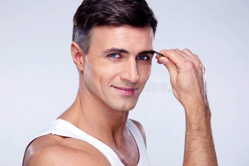 Homem que remove os cabelos da sobrancelha com arrancar imagem de stock royalty free