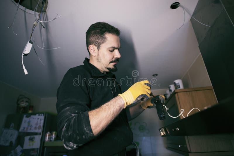 Homem que repainring a luz elétrica na cozinha da casa, interna imagens de stock