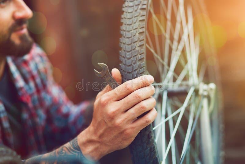 Homem que repara a bicicleta fotos de stock royalty free