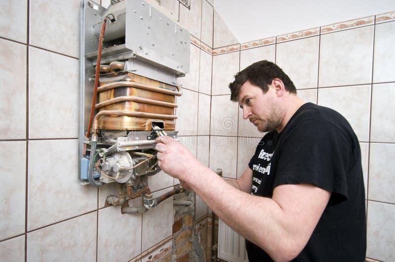 Homem que repara a fornalha de gás foto de stock royalty free