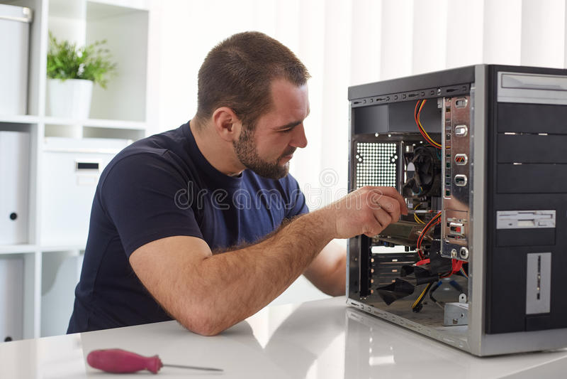 Homem que repara o computador imagem de stock