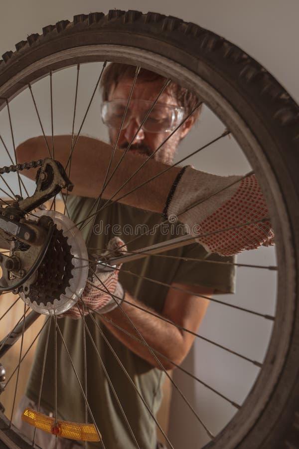 Homem que repara o Mountain bike velho na oficina fotos de stock royalty free