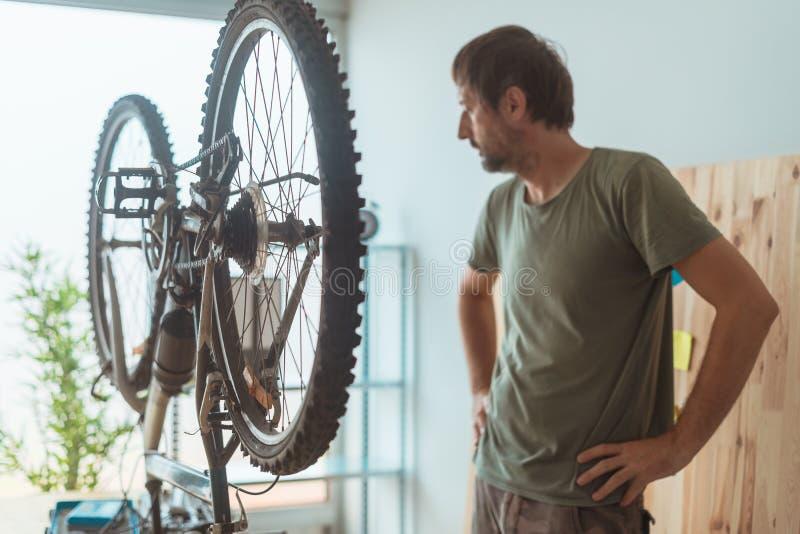 Homem que repara o Mountain bike velho na oficina fotografia de stock royalty free