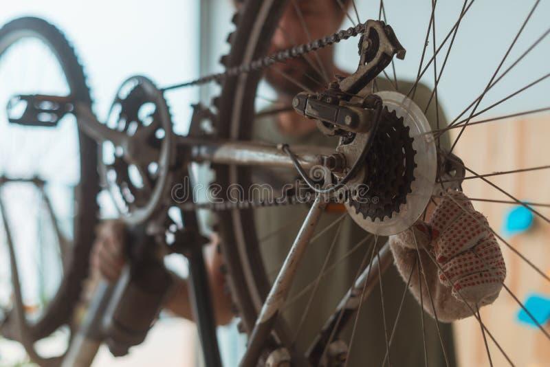 Homem que repara o Mountain bike velho na oficina imagem de stock