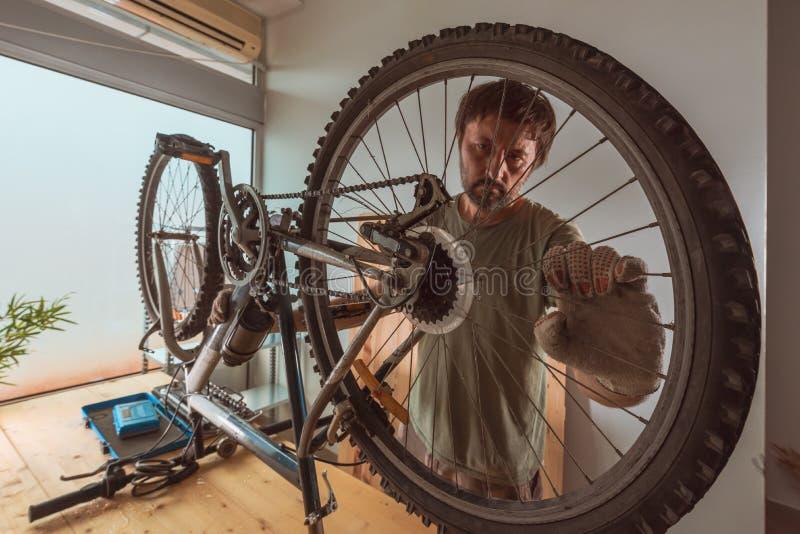 Homem que repara o Mountain bike velho na oficina imagens de stock