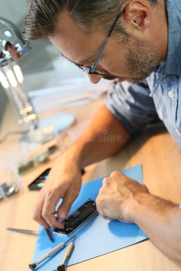 Homem que repara o smartphone na oficina foto de stock royalty free