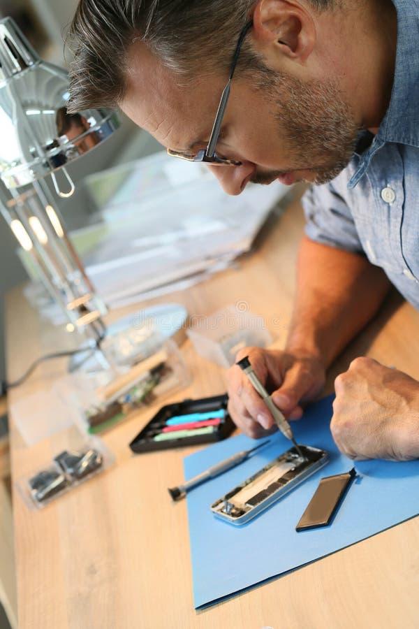 Homem que repara o smartphone na oficina fotografia de stock