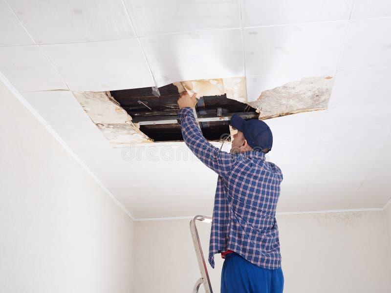 Homem que repara o teto desmoronado fotografia de stock royalty free