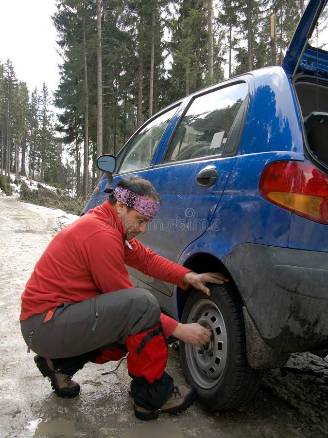 Homem que resolve uma punctura do pneumático fotografia de stock