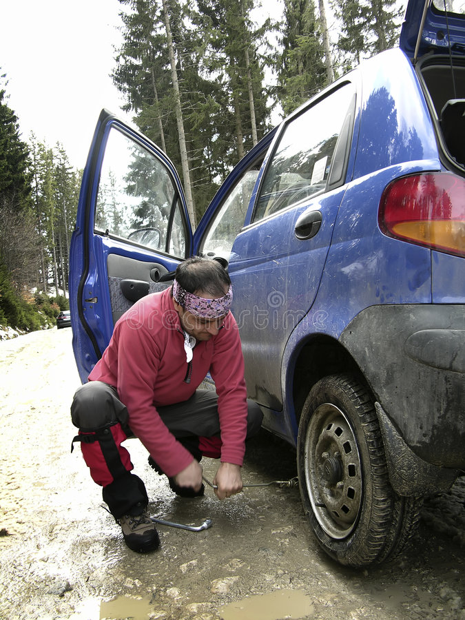 Homem que resolve uma punctura do pneumático imagens de stock