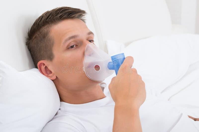 Homem que respira através da máscara do inalador imagens de stock