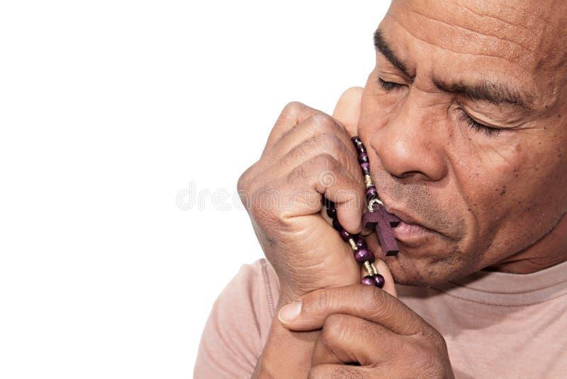 Homem que reza ao deus com os grânulos do rosário em suas mãos foto de stock royalty free