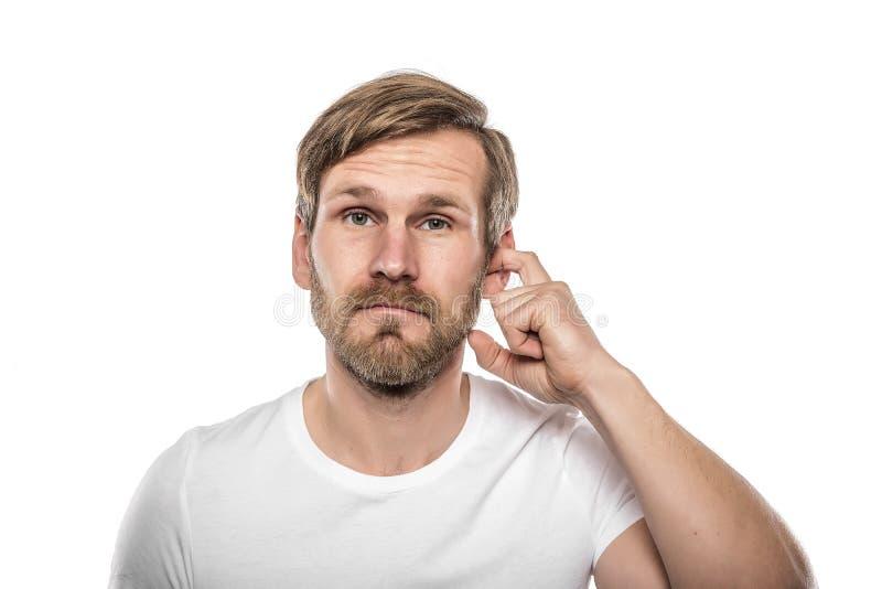 Homem que risca em sua orelha fotografia de stock royalty free