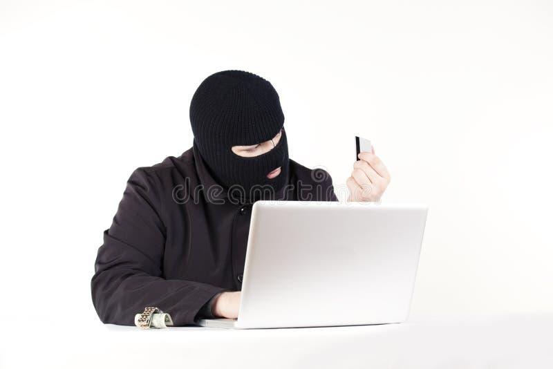 Homem que rouba dados de um portátil fotografia de stock