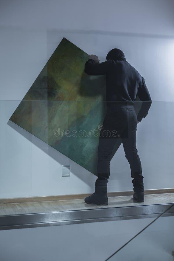 Homem que rouba a obra de arte imagens de stock