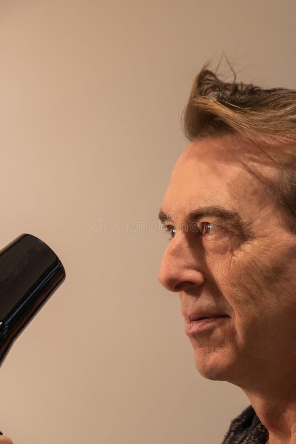 Homem que seca seu cabelo com um hairdryer foto de stock royalty free