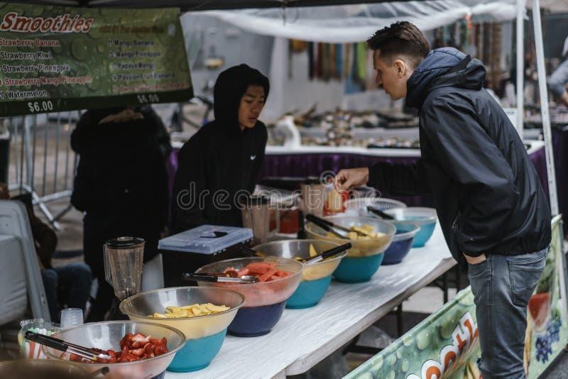 Homem que seleciona seu alimento em um suporte da rua em New York imagens de stock royalty free