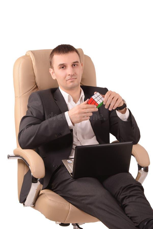 Homem que senta-se com o cubo de um Rubik fotos de stock royalty free