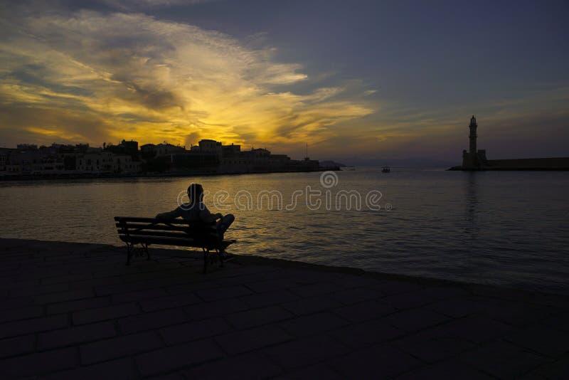 Homem que senta-se contra o mar no por do sol foto de stock
