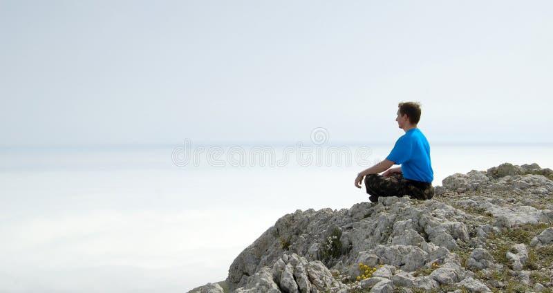 Homem que senta-se em Lotus Position na rocha acima do mar fotos de stock