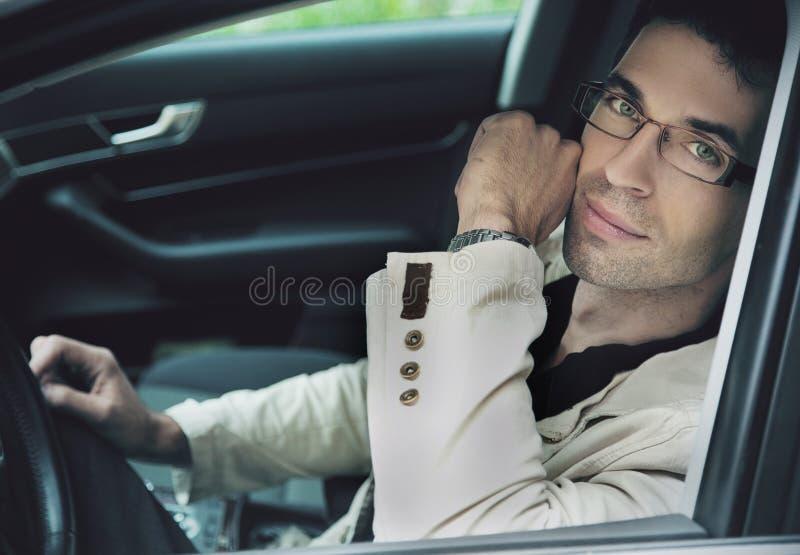 Homem que senta-se em um carro imagem de stock