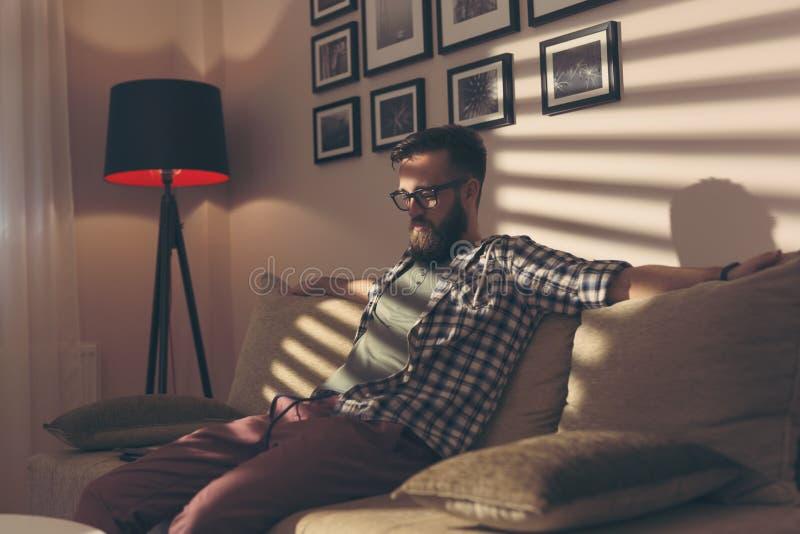 Homem que senta-se em um sofá foto de stock royalty free