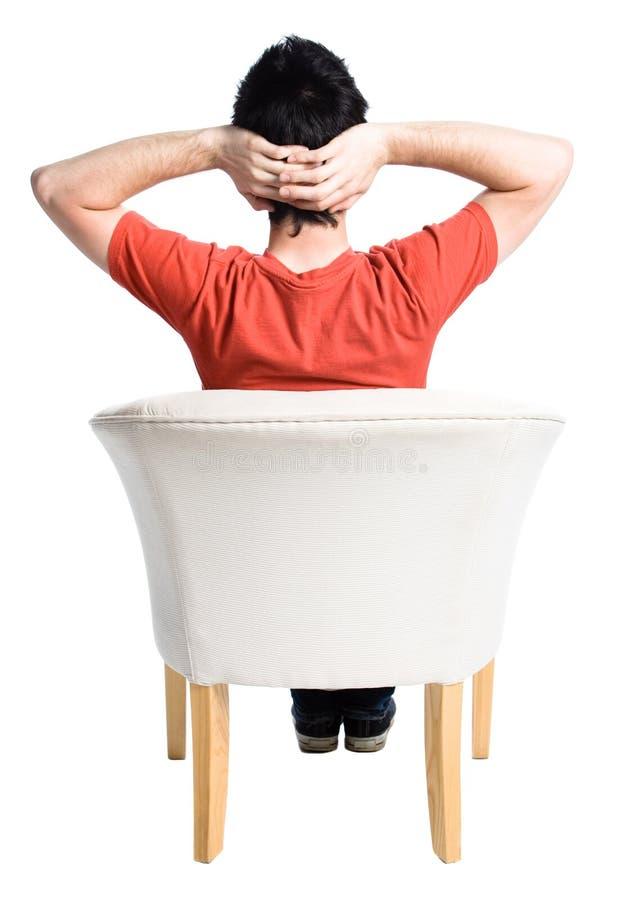 Homem que senta-se em uma cadeira imagem de stock