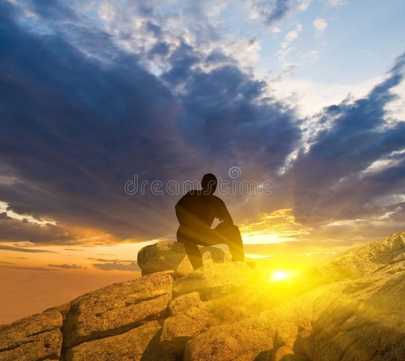 Homem que senta-se em uma parte superior da montanha imagens de stock royalty free