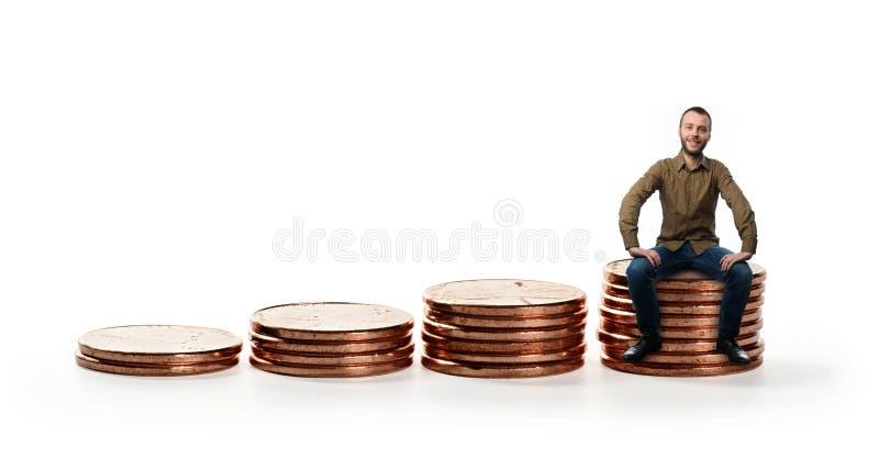 Homem que senta-se em uma pilha de moedas imagens de stock